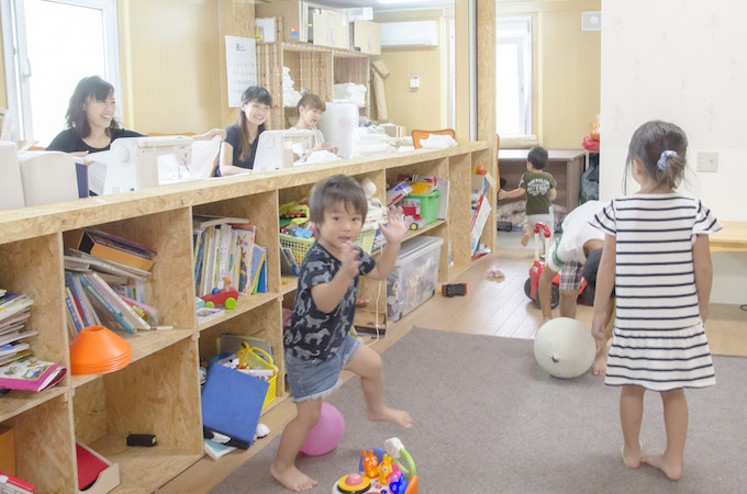ベビーモスリンの縫製をするお母さんと、棚で仕切られたキッズスペースで遊ぶ子どもたち。目の合う距離だから、子どももお母さんも安心です。