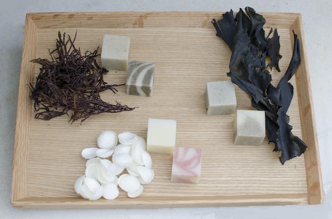 原材料と石けん。ふのり(左上)、シルク(中央)、干しわかめ(右上)。