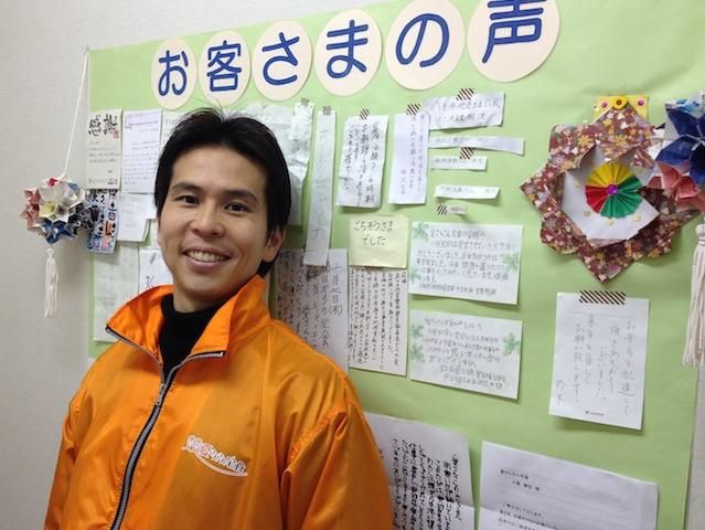 愛さんさん宅食株式会社代表の小尾勝吉さん。お客様の声が壁一面に掲示されている。感謝と喜びのメッセージだ。